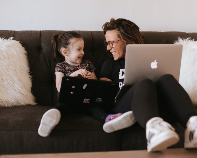 Martha sitting with her daughter on a couch while working on her Macbook