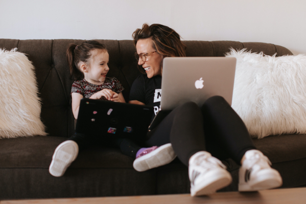 Martha smiling at her daughter while on a couch with her Macbook