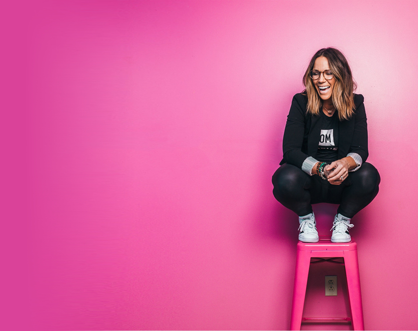 Martha Krejci posing in front of a pink background on a bright pink stool